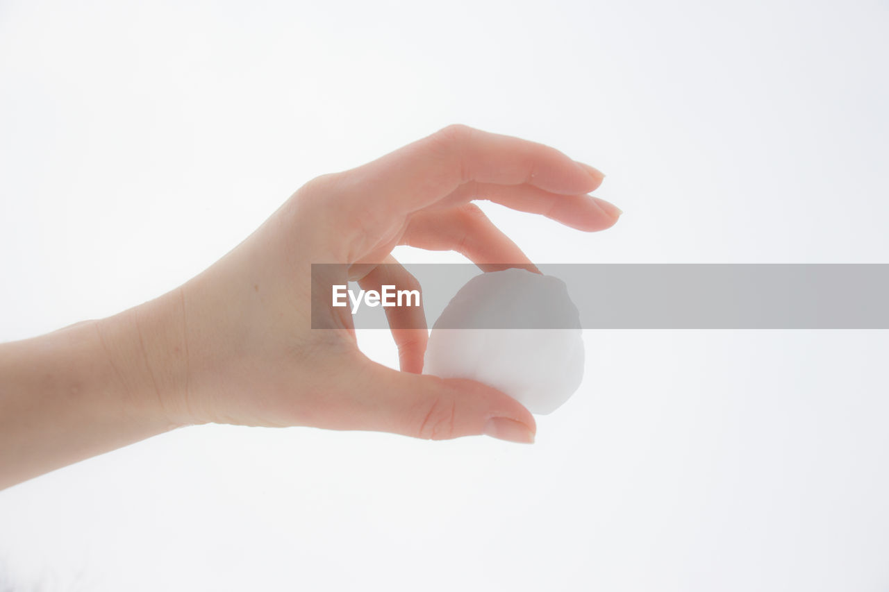 HUMAN HAND HOLDING BALL AGAINST WHITE BACKGROUND