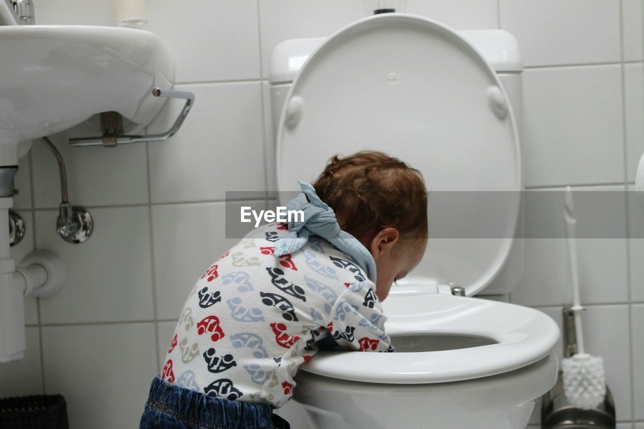 Rear view of boy with hands in toilet