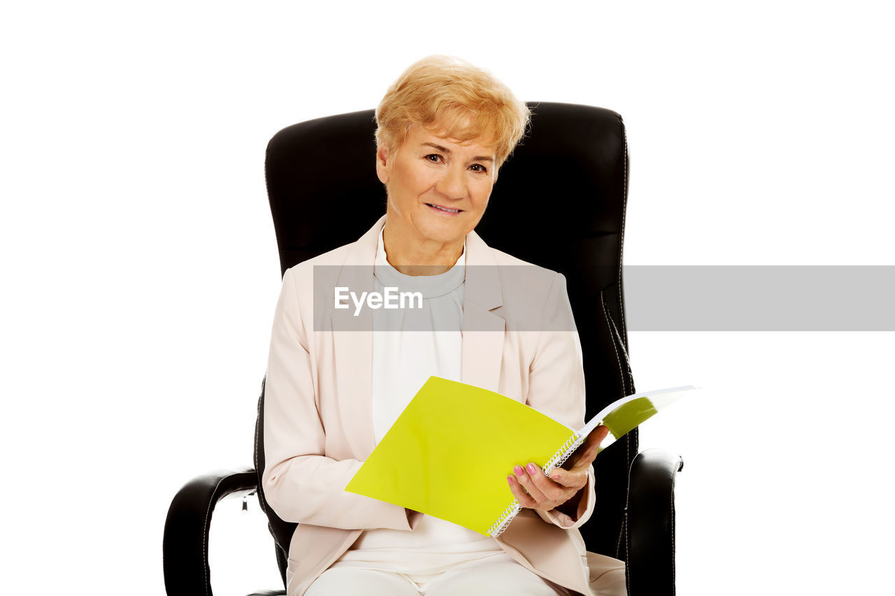 Portrait of senior businesswoman with book sitting on chair against white background