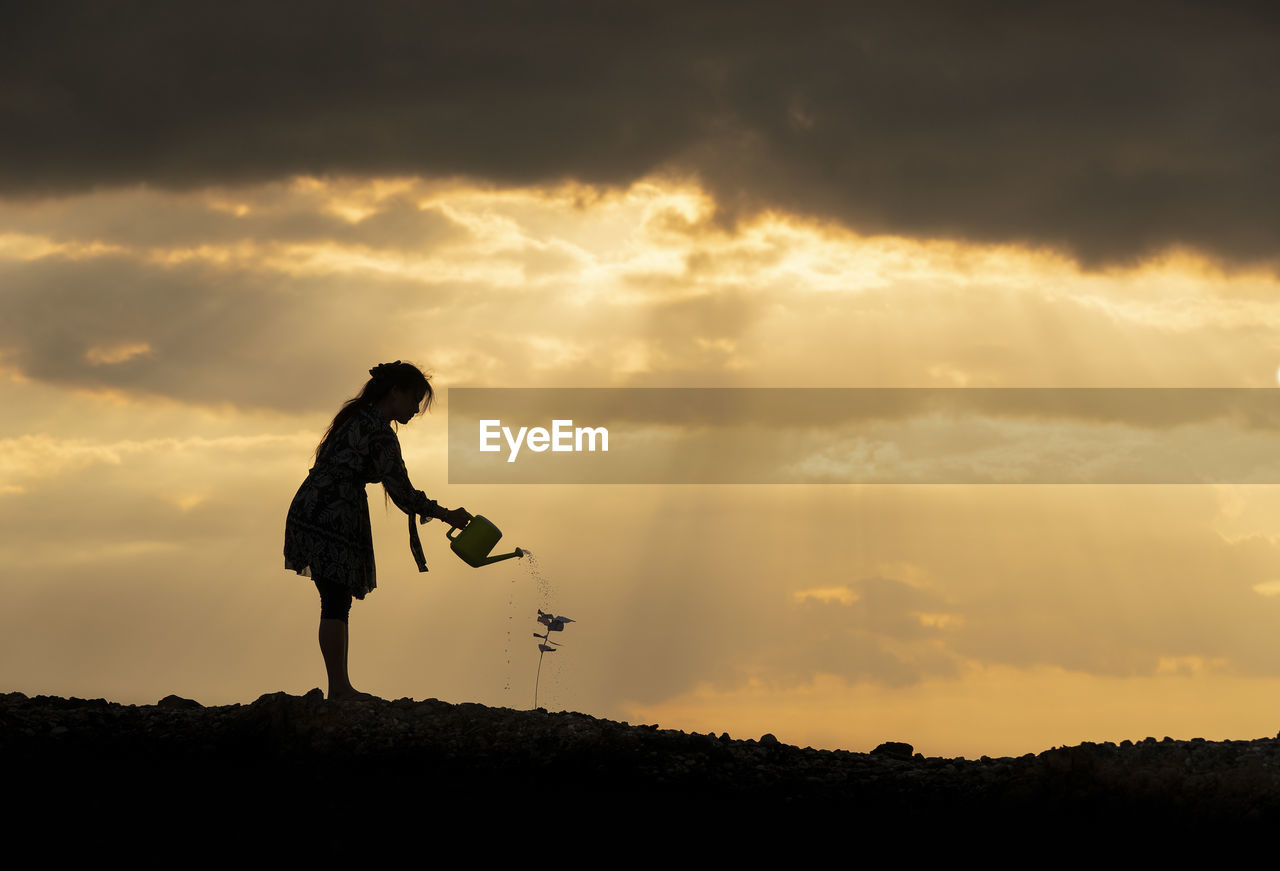 Silhouette woman watering plant on land against sky at sunset