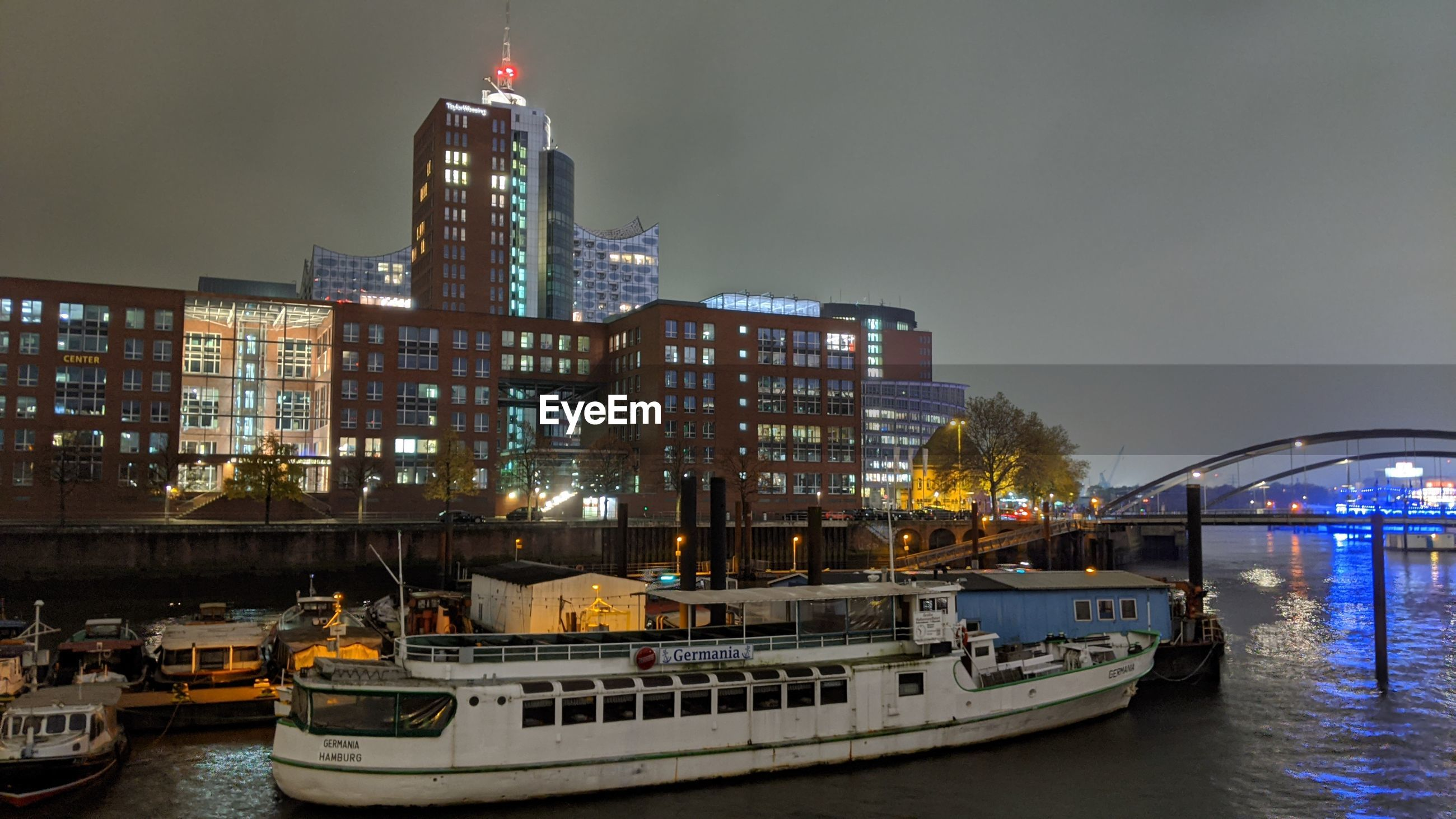 BOATS IN RIVER BY ILLUMINATED BUILDINGS AGAINST SKY