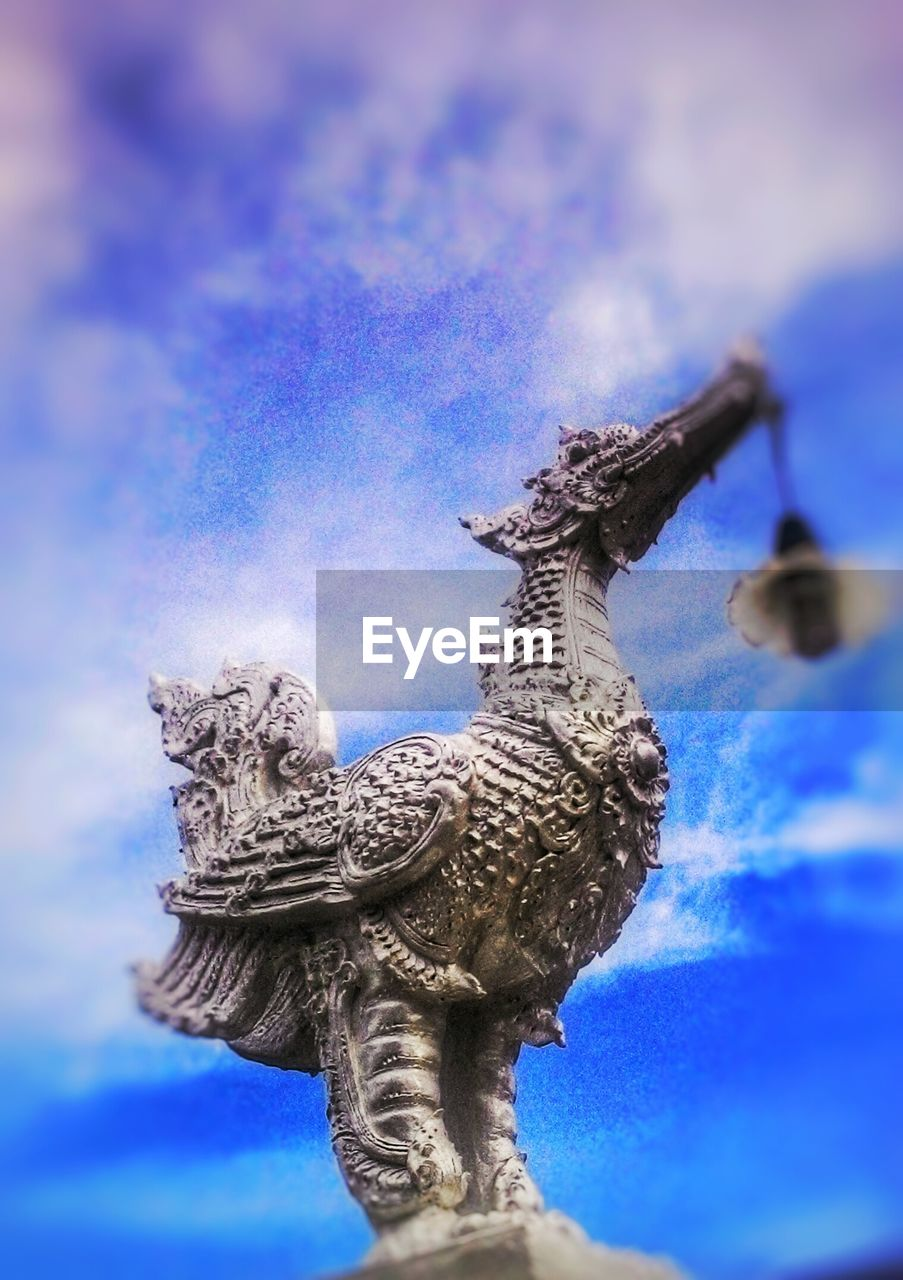 sculpture, statue, art and craft, animal representation, low angle view, no people, sky, cloud - sky, day, outdoors, blue, nature, animal themes