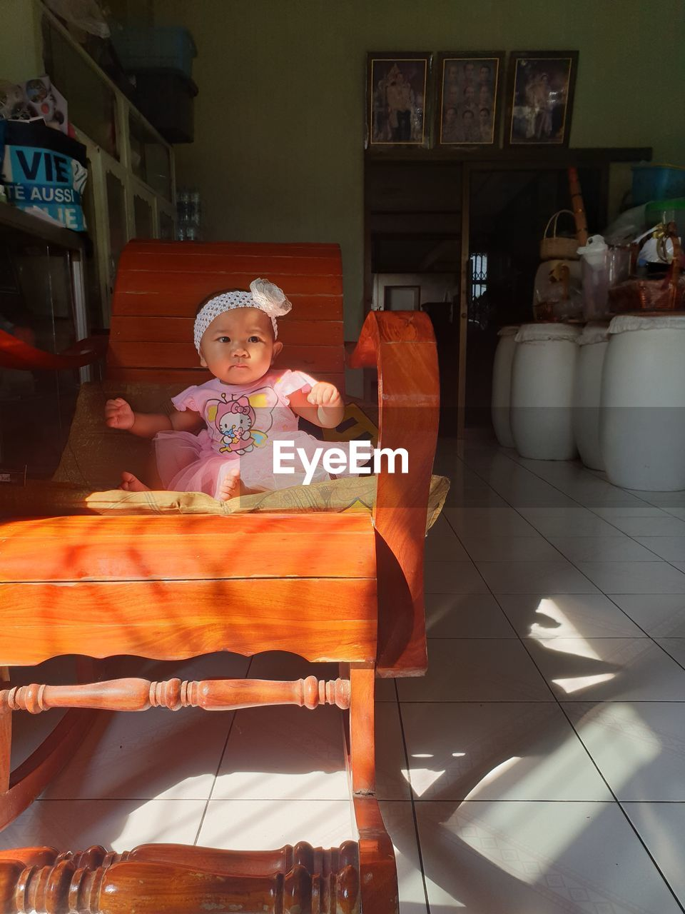 PORTRAIT OF CUTE GIRL SITTING ON CHAIR IN KITCHEN