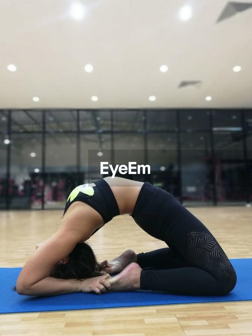 Mid Adult Woman Doing Yoga At Studio