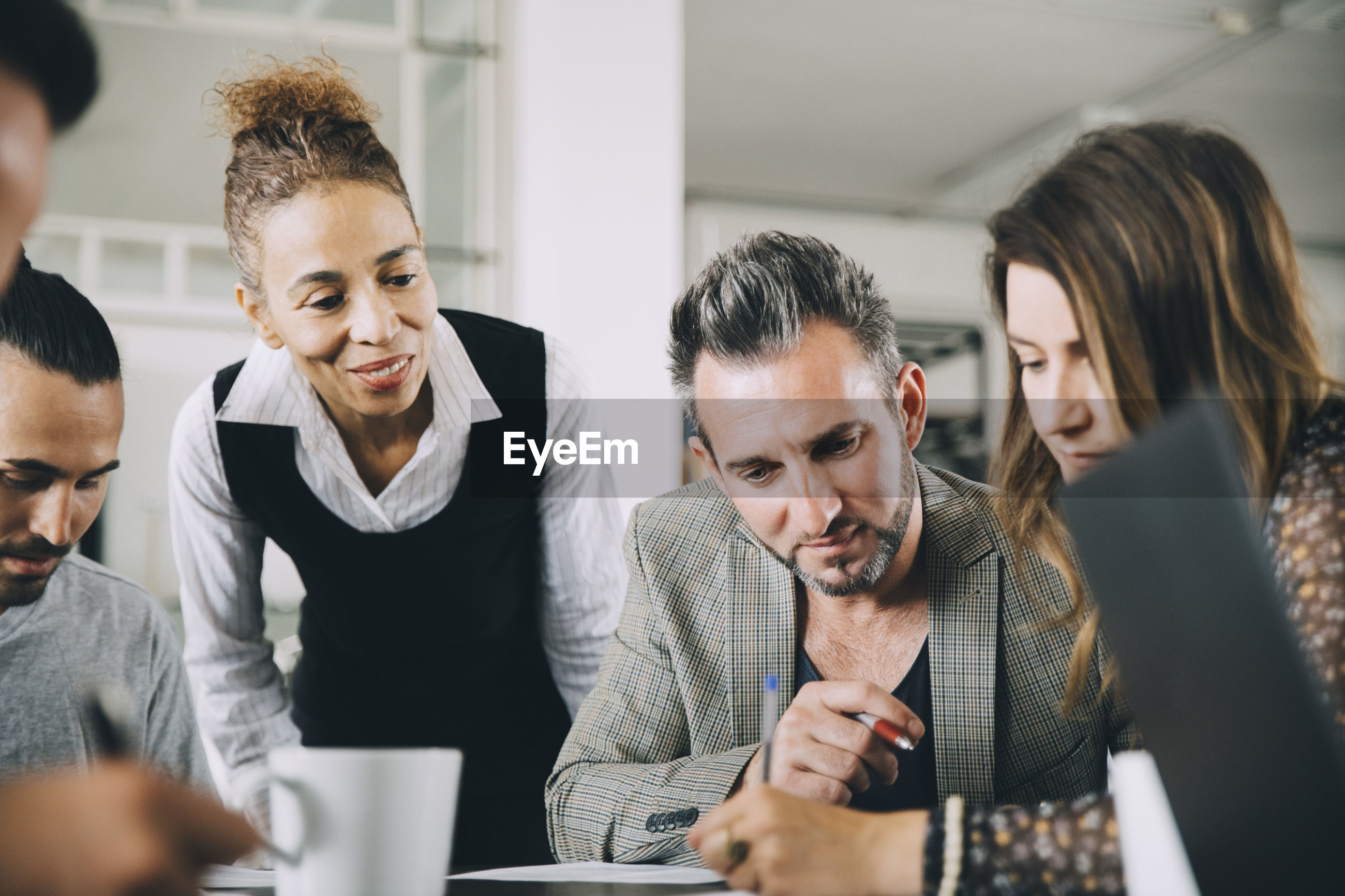 GROUP OF PEOPLE WORKING ON TABLE IN OFFICE