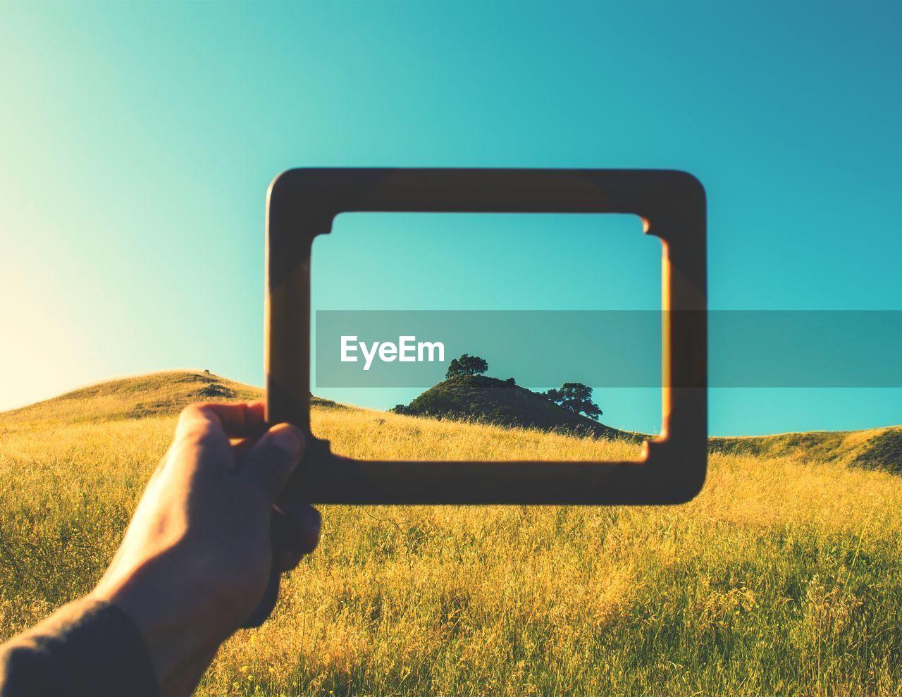 Man Holding Frame On Grassy Field