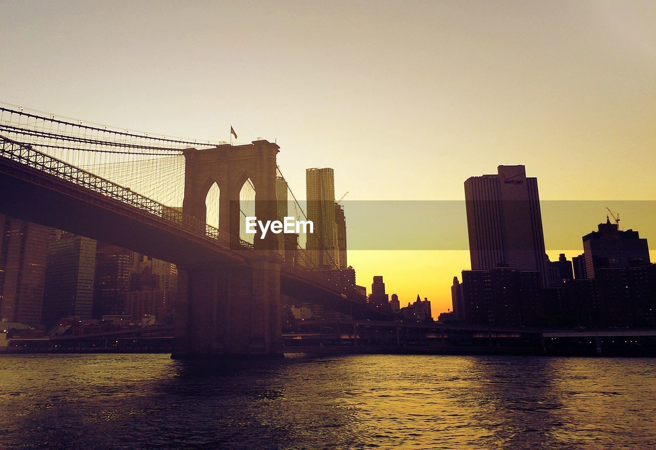 Low angle view of brooklyn bridge over river against clear sky during sunset in city