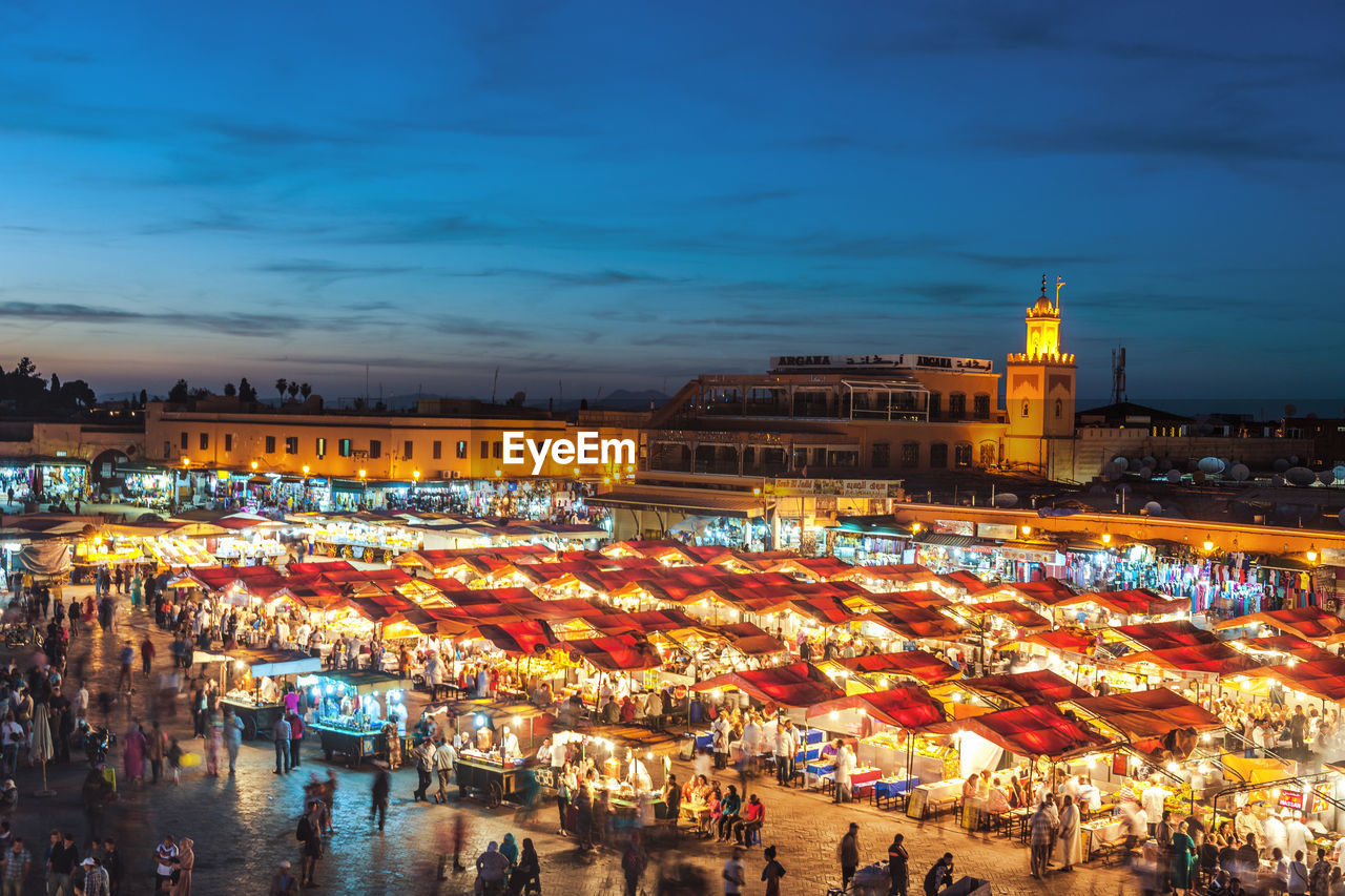 illuminated, architecture, building exterior, built structure, night, crowd, city, market, sky, market stall, dusk, nature, high angle view, group of people, large group of people, cloud - sky, travel destinations, business, retail, real people, outdoors, light, cityscape, street market, nightlife