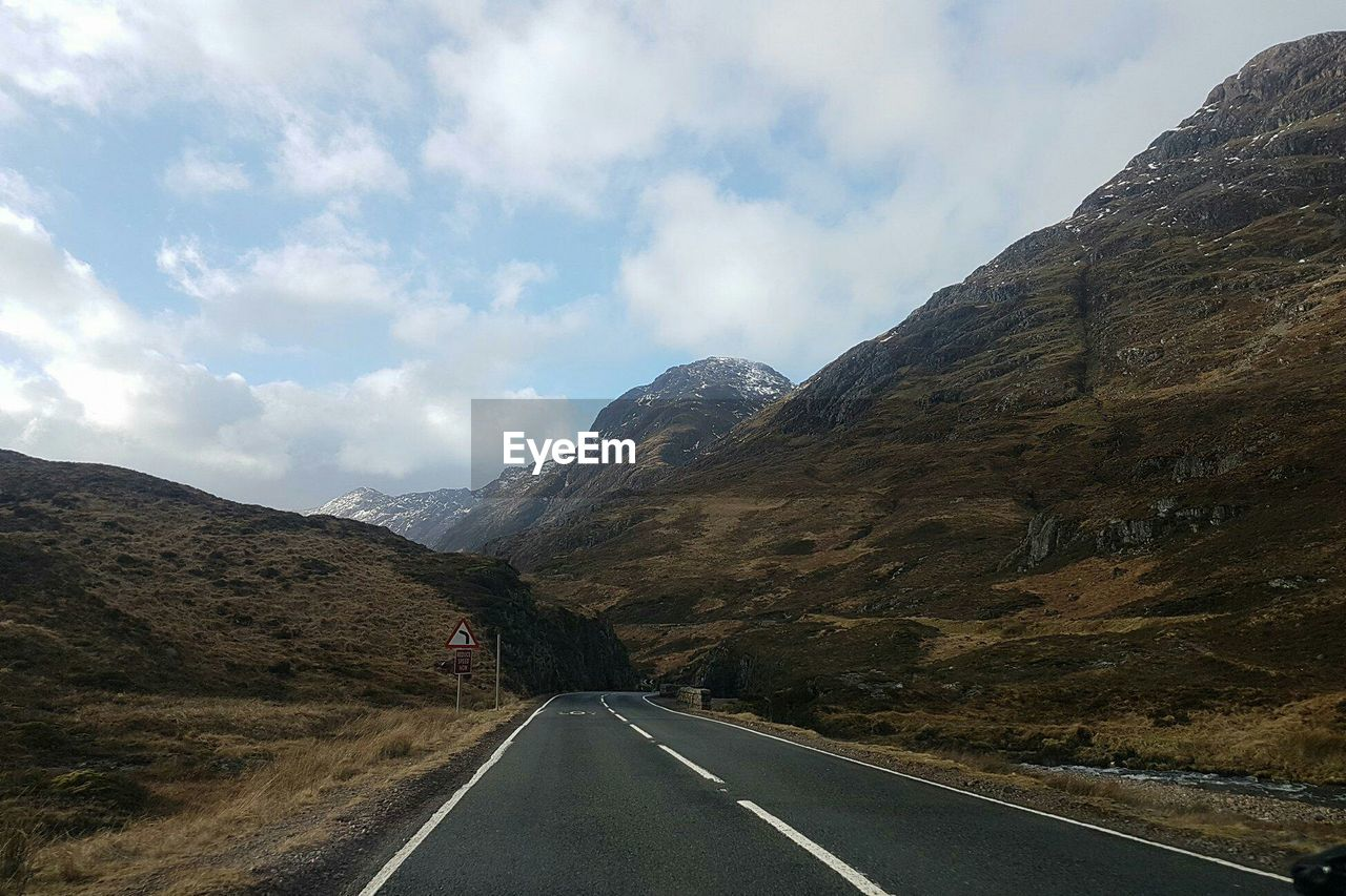 road, transportation, mountain, sky, cloud - sky, direction, the way forward, scenics - nature, symbol, mountain range, beauty in nature, road marking, marking, non-urban scene, nature, landscape, sign, environment, no people, tranquil scene, diminishing perspective, dividing line, outdoors, formation, long