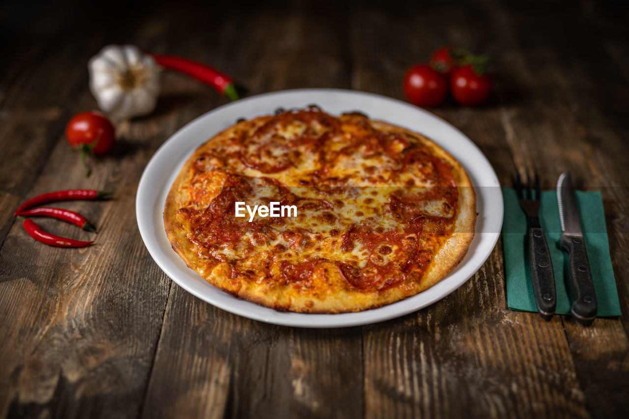 food, food and drink, table, ready-to-eat, still life, indoors, freshness, pizza, no people, wood - material, vegetable, close-up, red, italian food, high angle view, tomato, kitchen utensil, focus on foreground, healthy eating, plate, temptation, place mat