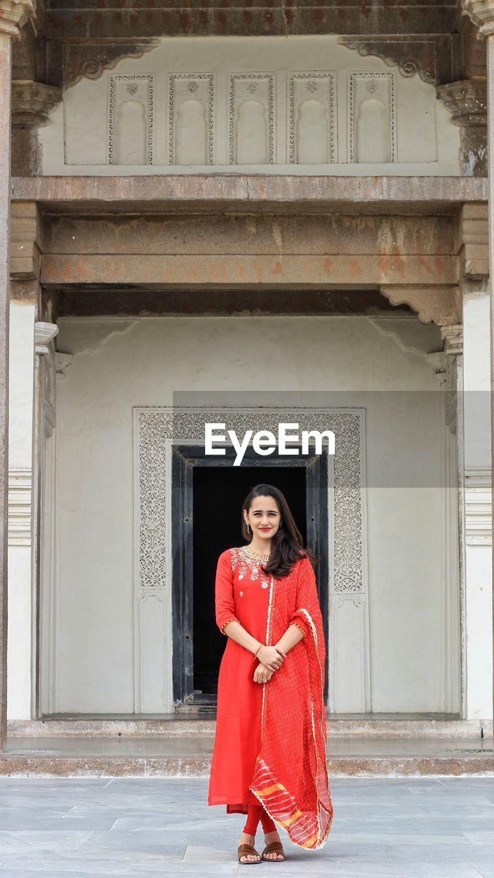 red, looking at camera, architecture, one person, young adult, building exterior, standing, full length, smiling, real people, portrait, adult, built structure, day, entrance, women, clothing, beautiful woman, young women, front view, outdoors, architectural column, hairstyle
