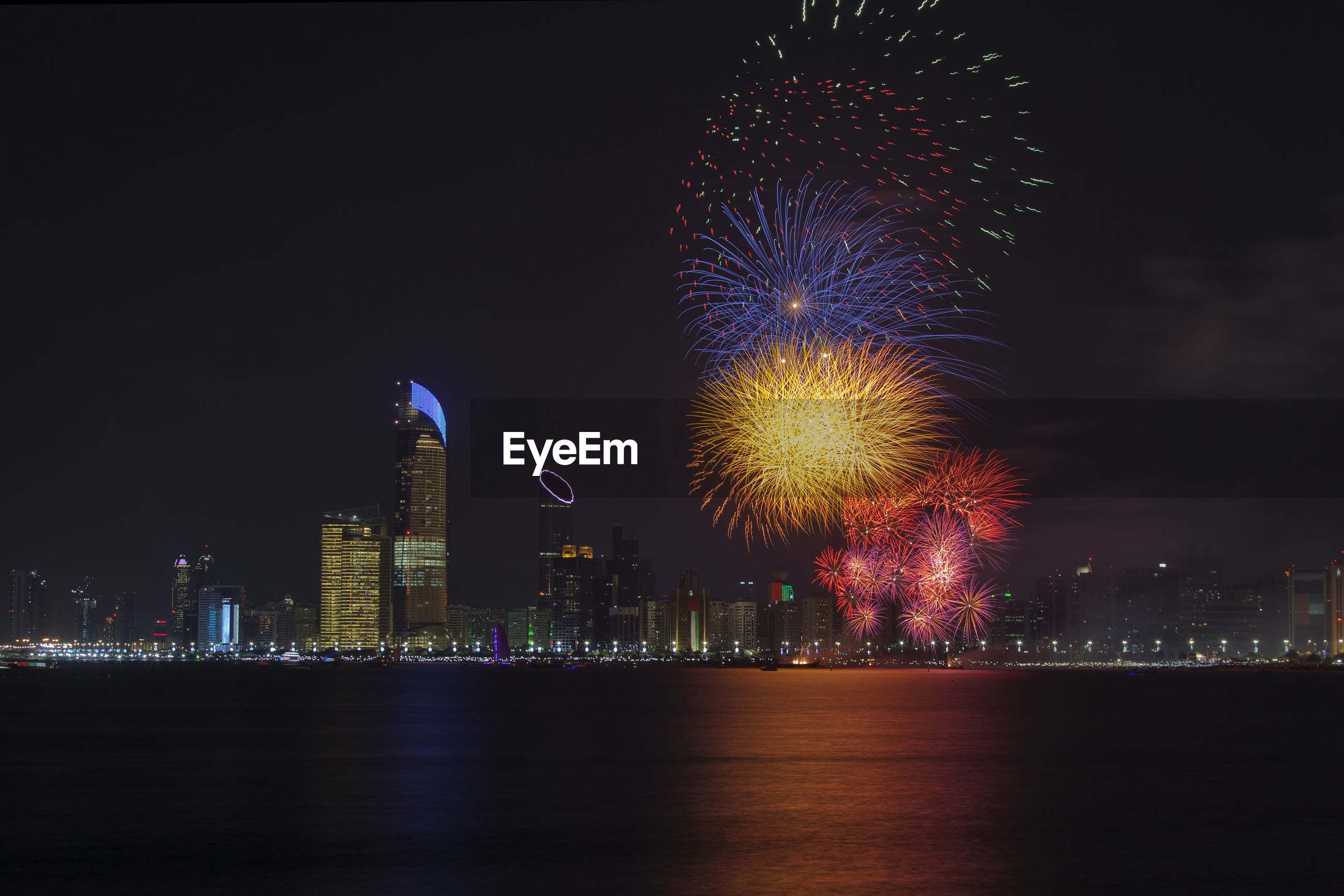 Firework display over river against sky in city at night