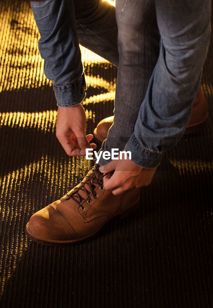 Low section of man tying shoelace on floor