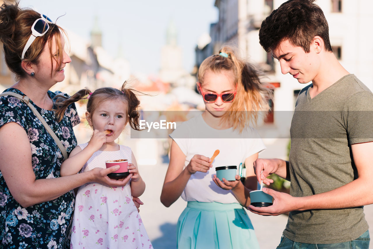 Mother and children having ice cream in city during sunny day