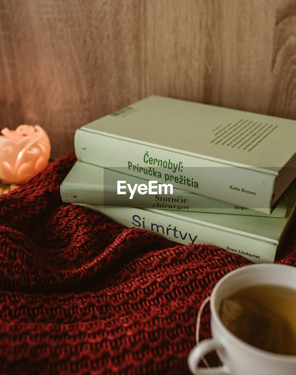 CLOSE-UP OF COFFEE CUP WITH BOOK AND TEXT ON TABLE