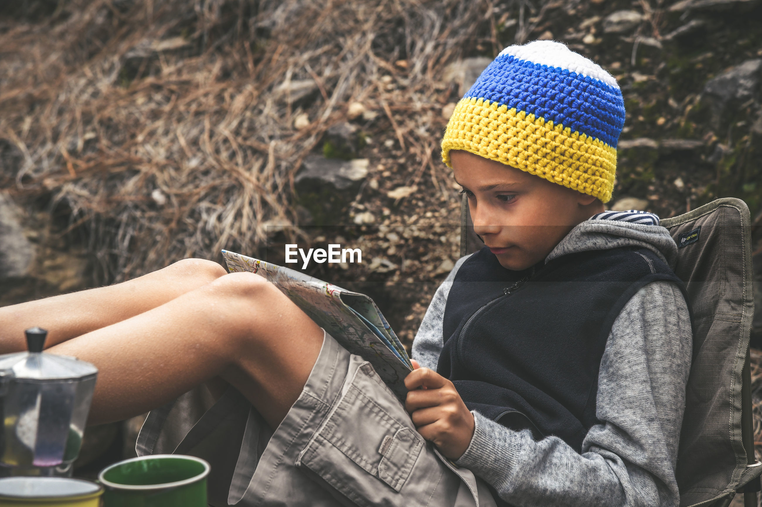 Boy reading map while relaxing on chair at forest