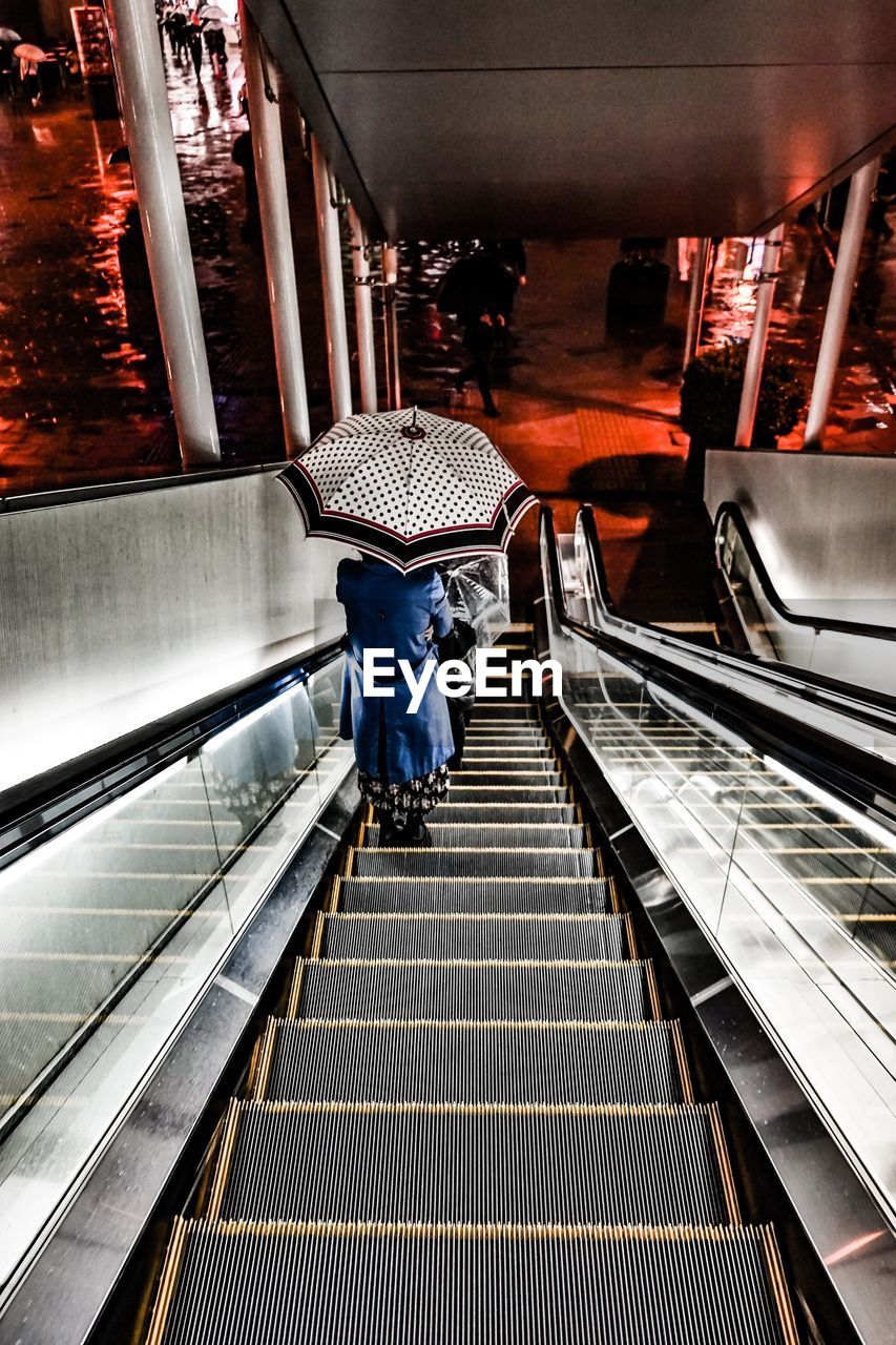 real people, rear view, steps, railing, full length, lifestyles, escalator, staircase, steps and staircases, walking, one person, built structure, the way forward, leisure activity, men, architecture, women, casual clothing, standing, transportation, indoors, technology, illuminated, day, hand rail