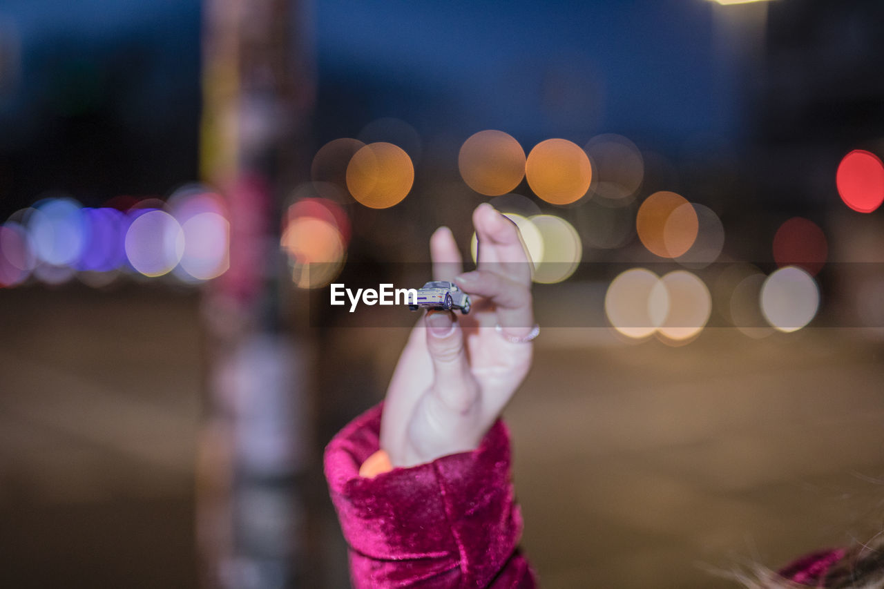 illuminated, focus on foreground, night, one person, human hand, lens flare, human body part, holding, real people, hand, close-up, lifestyles, glowing, leisure activity, city, body part, unrecognizable person, defocused, light - natural phenomenon, finger, purple