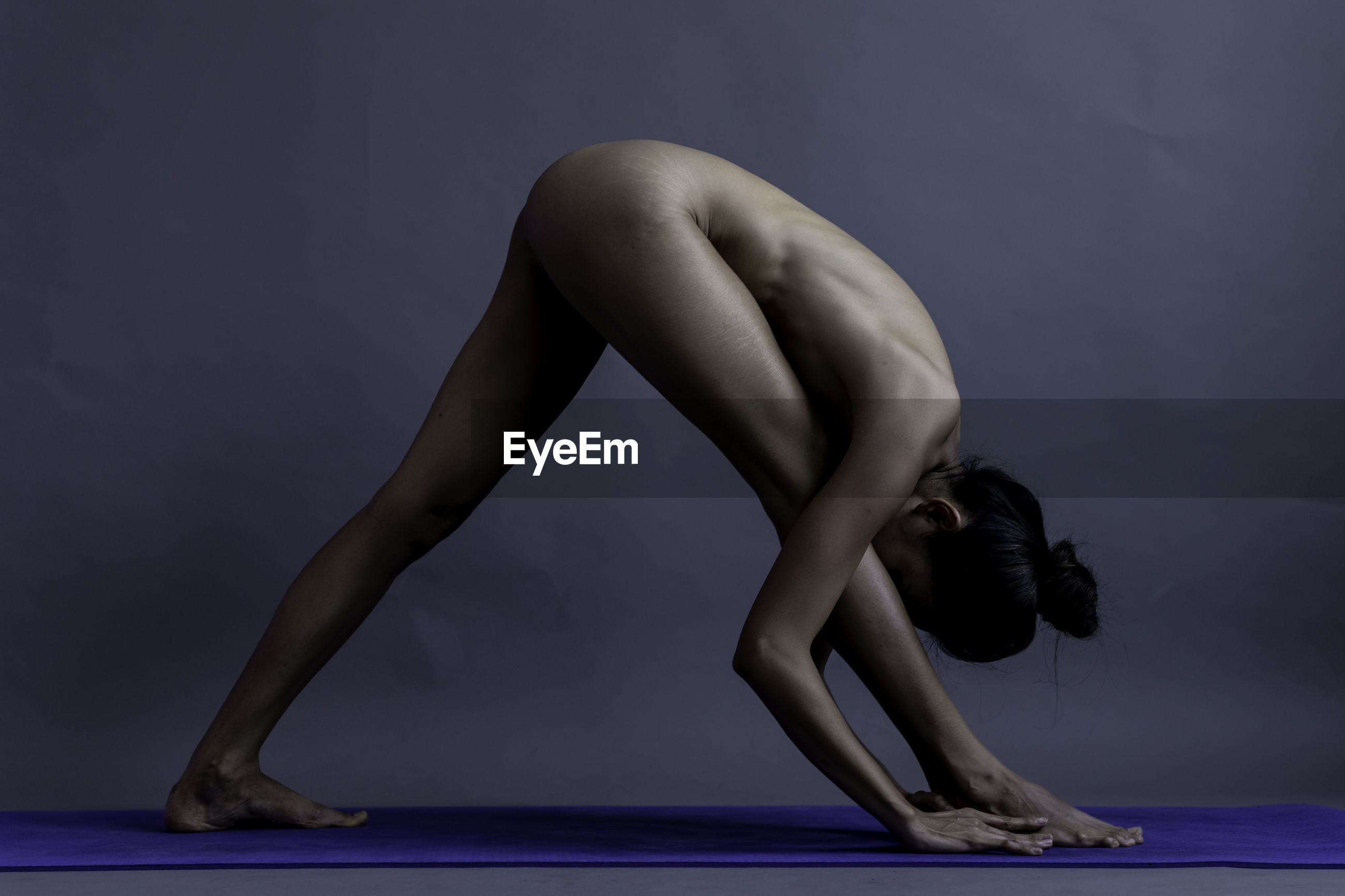 Full length of naked woman exercising against gray background