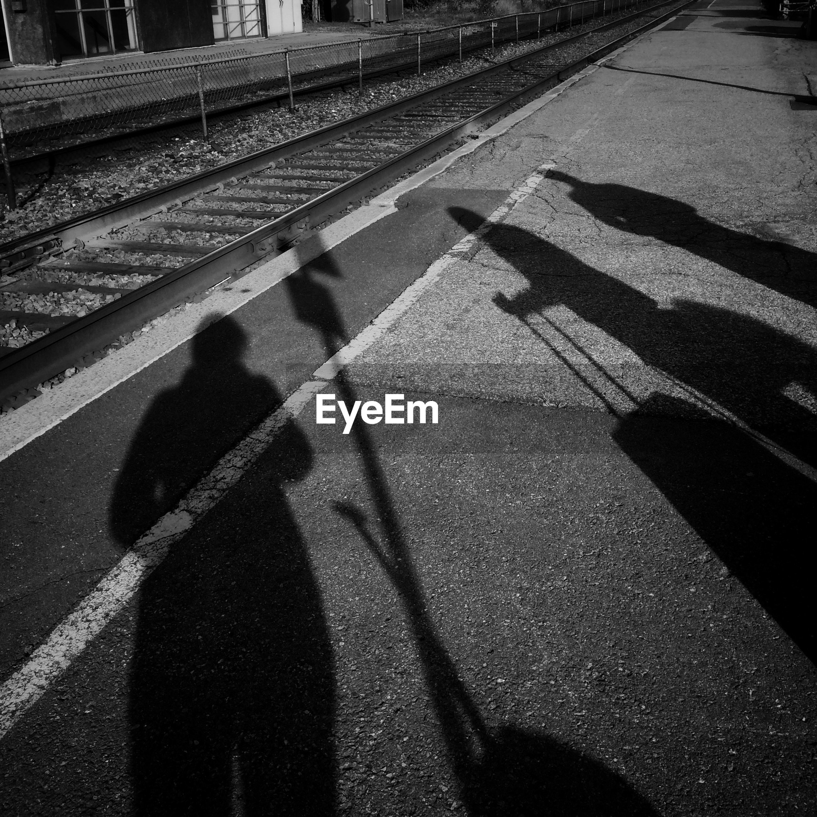Shadow of people falling on railroad station platform