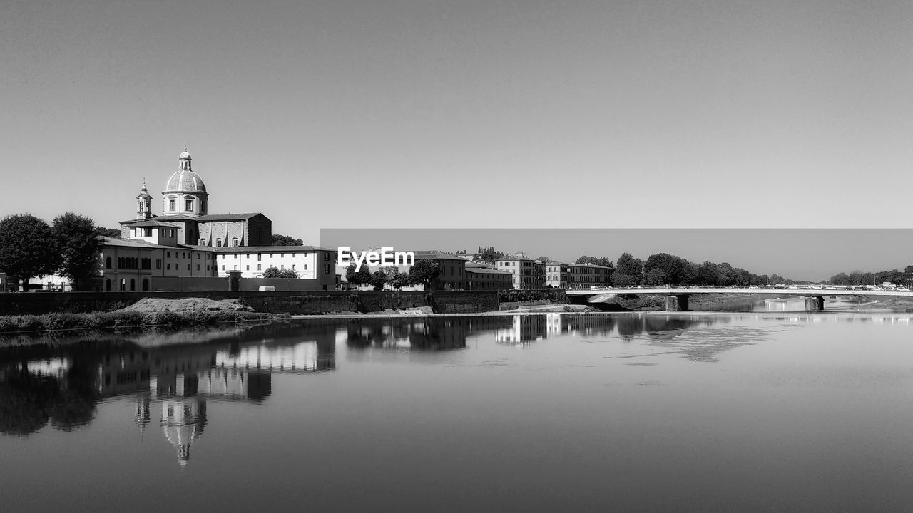 Reflection Of Dome And Buildings On Arno River Against Clear Sky