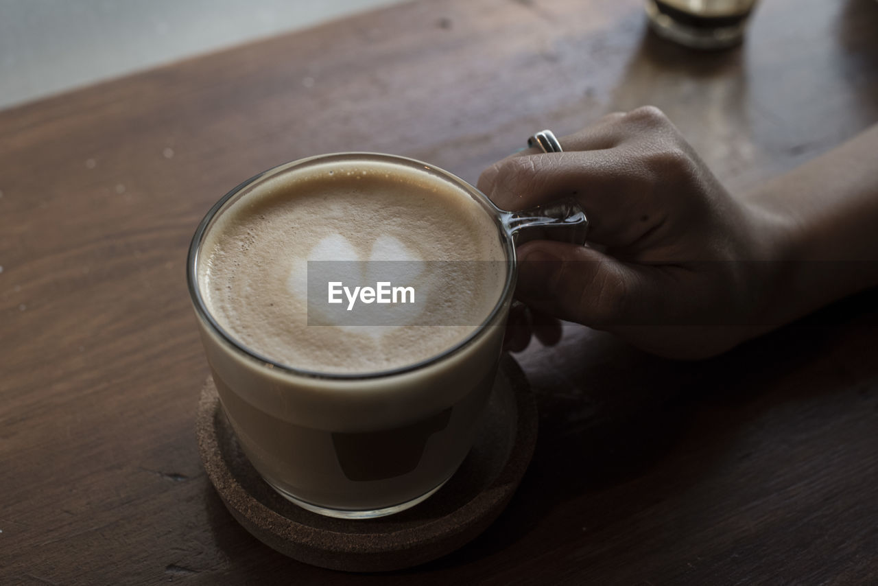 coffee, drink, cup, coffee - drink, refreshment, coffee cup, mug, human hand, food and drink, table, hand, human body part, real people, frothy drink, lifestyles, one person, indoors, leisure activity, still life, hot drink, body part, latte, finger, crockery, non-alcoholic beverage