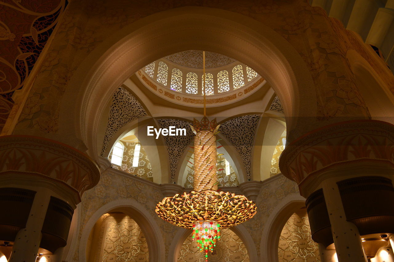 architecture, low angle view, built structure, indoors, building, architectural column, ceiling, pattern, lighting equipment, arch, no people, ornate, design, place of worship, religion, illuminated, art and craft, architectural feature, travel destinations, hanging, electric lamp, architecture and art, floral pattern