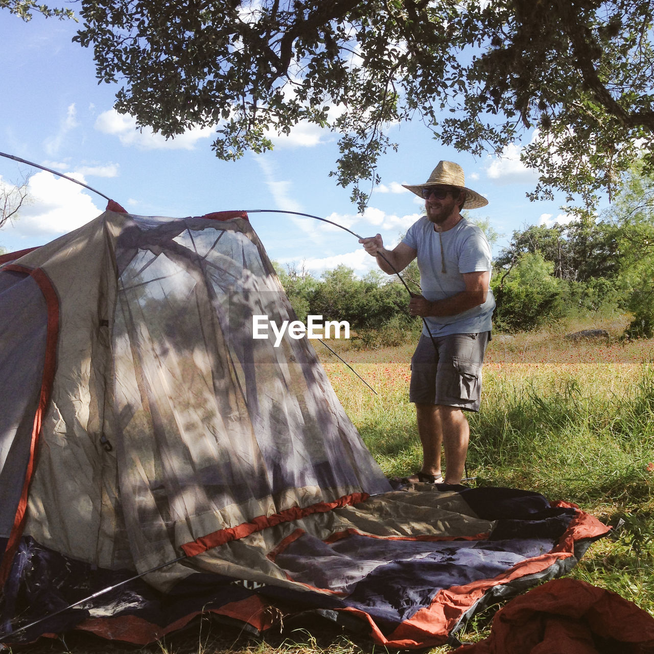 Man Wearing Hat While Putting Tent On Grassy Field