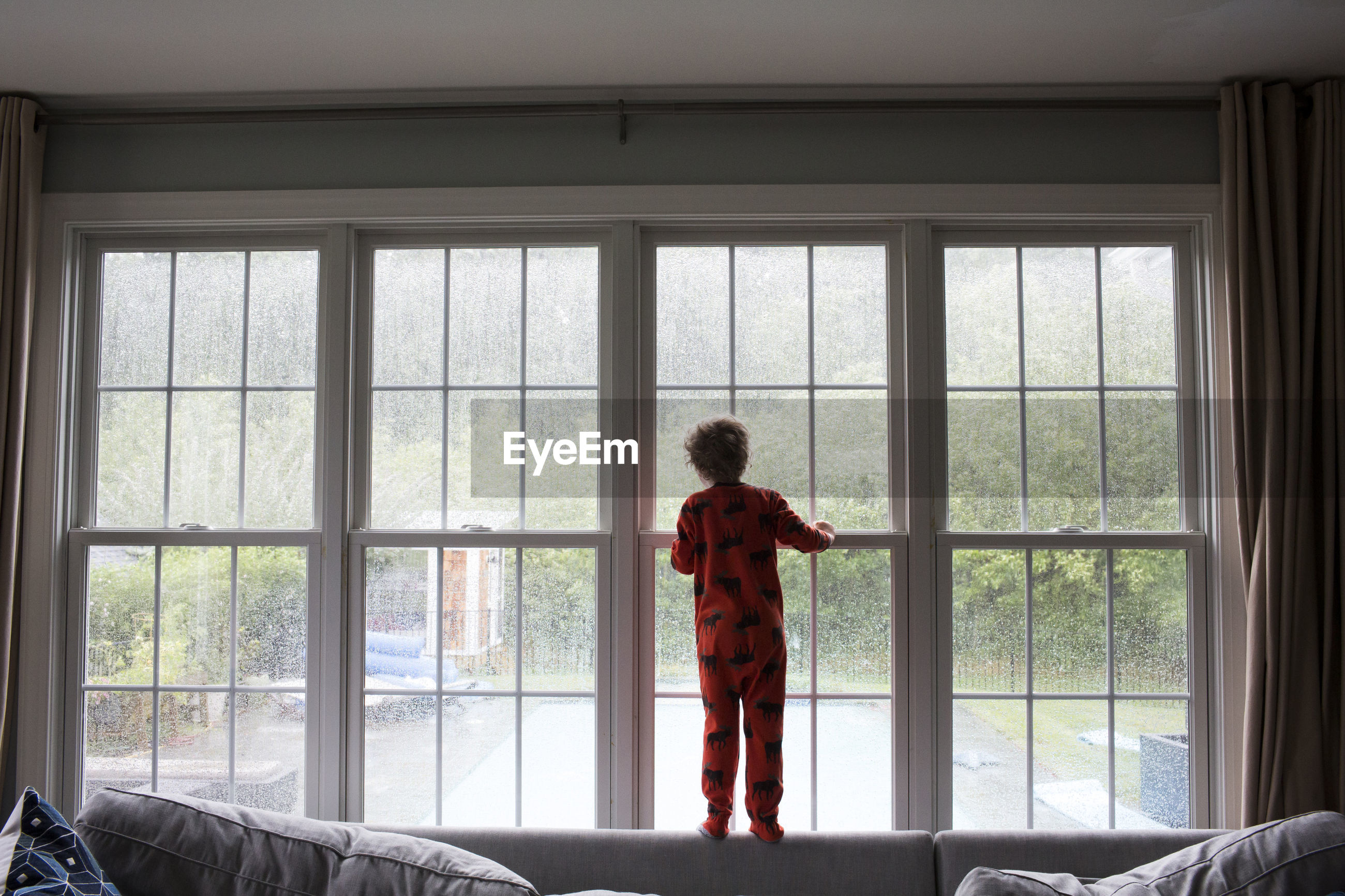 REAR VIEW OF A BOY LOOKING THROUGH WINDOW