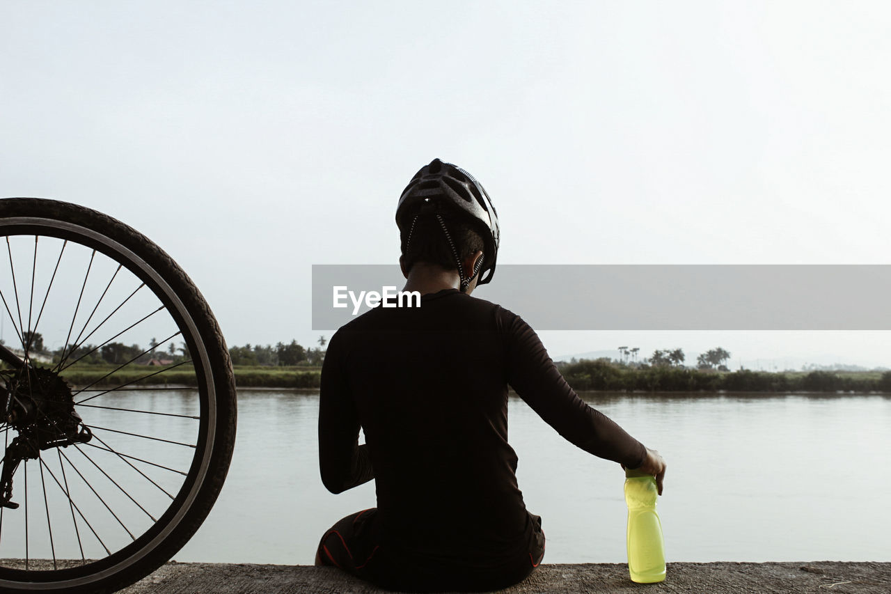 Rear View Of Cyclist Against River