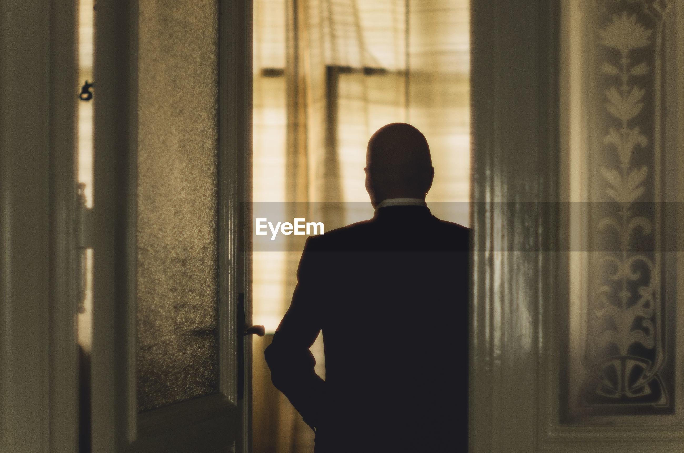 Rear view of businessman in suit standing by door