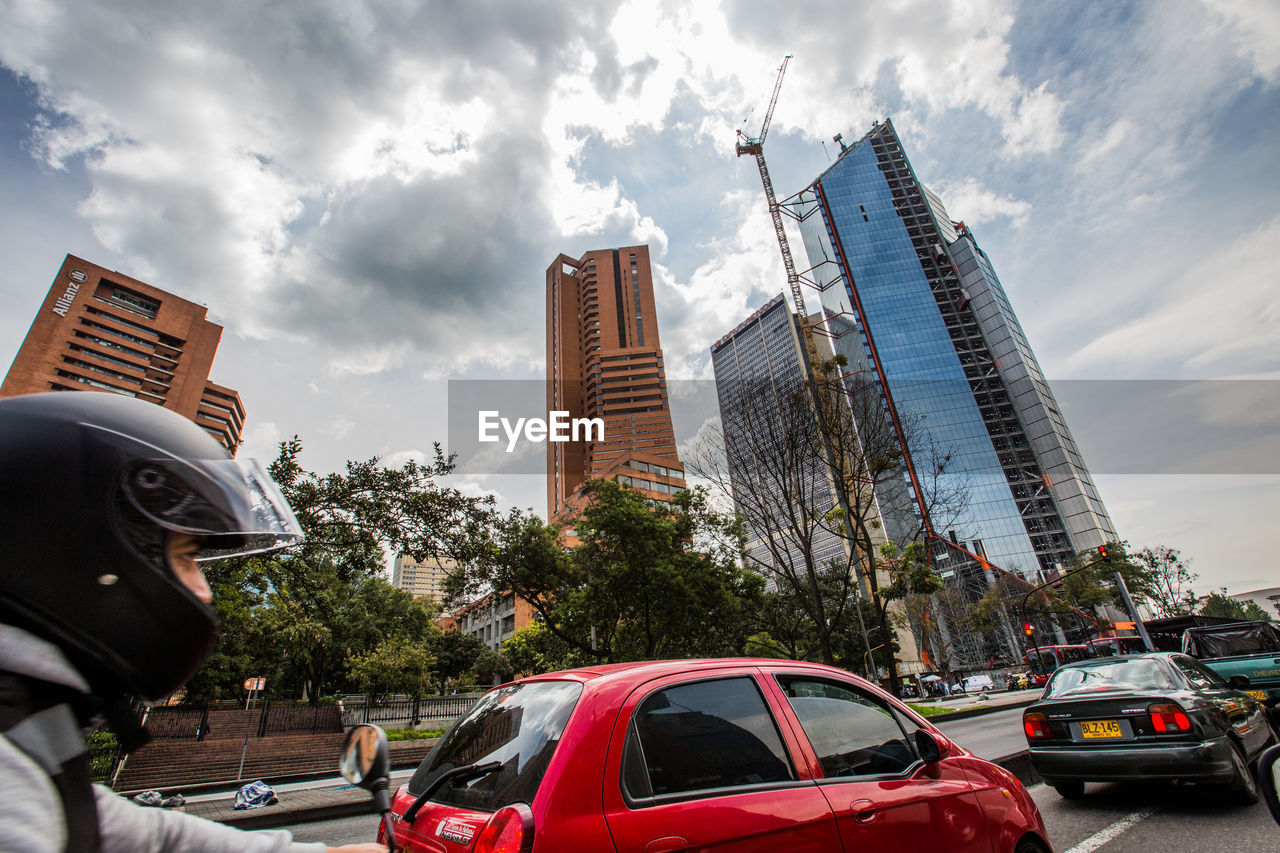 mode of transportation, transportation, city, car, architecture, motor vehicle, built structure, land vehicle, sky, building exterior, cloud - sky, day, nature, travel, tree, office building exterior, tower, incidental people, red, street, skyscraper