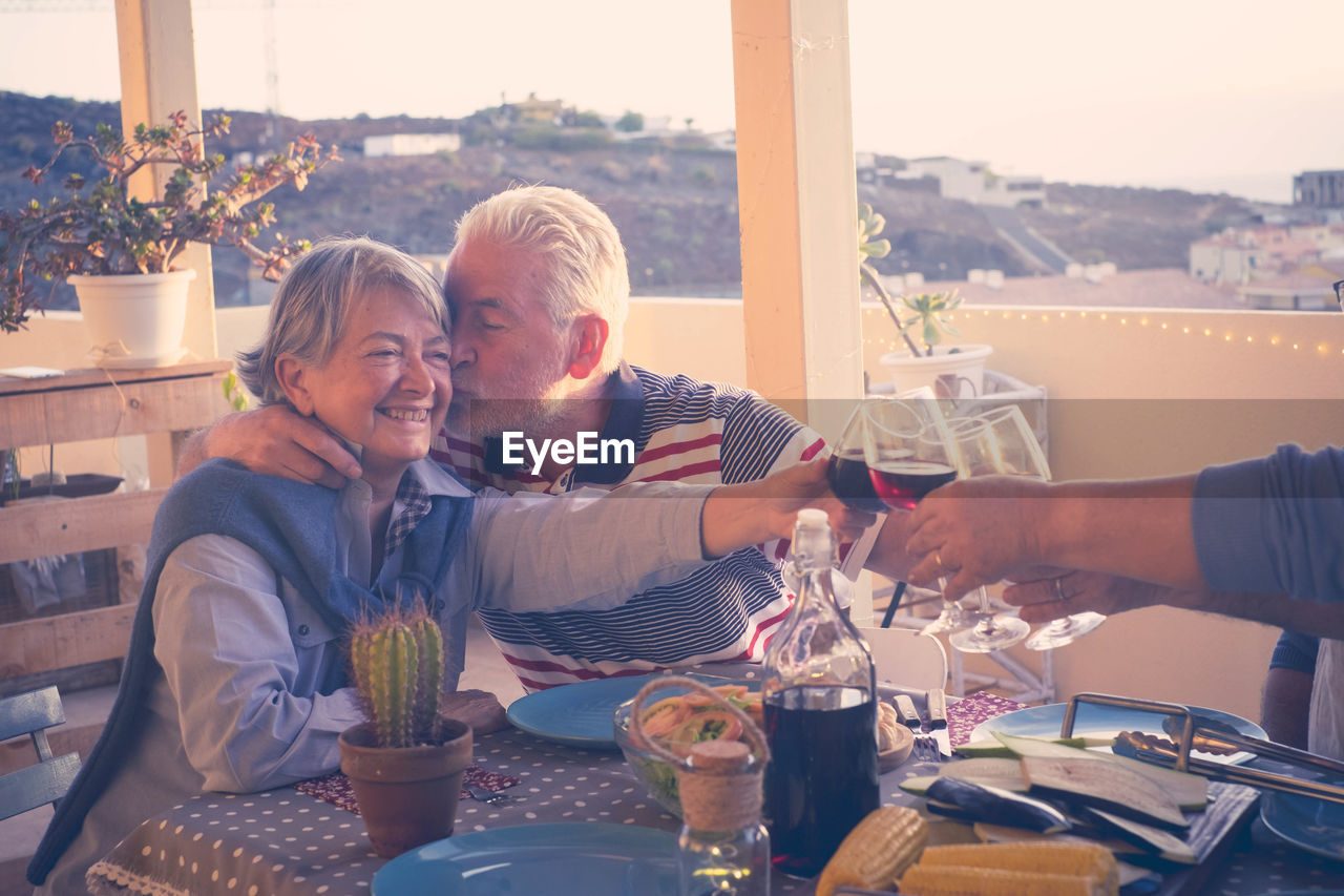 Senior Loving Couple Toasting Drinks With Friends At Restaurant
