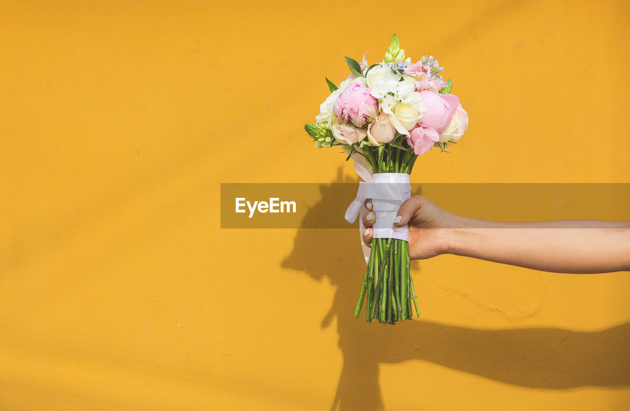 Cropped Hand Of Woman Holding Bouquet Against Yellow Wall