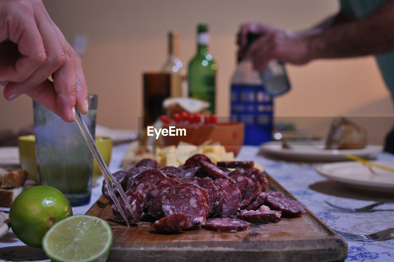food and drink, food, freshness, human hand, hand, table, fruit, real people, indoors, human body part, healthy eating, one person, cutting, lifestyles, cutting board, unrecognizable person, kitchen knife, focus on foreground, meat, holding, preparation, temptation