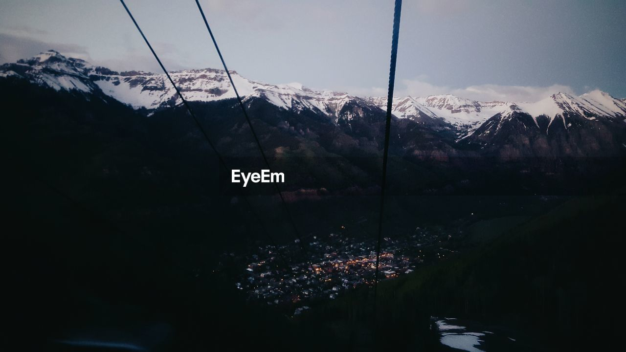 High angle view of town at beneath of snowcapped mountain