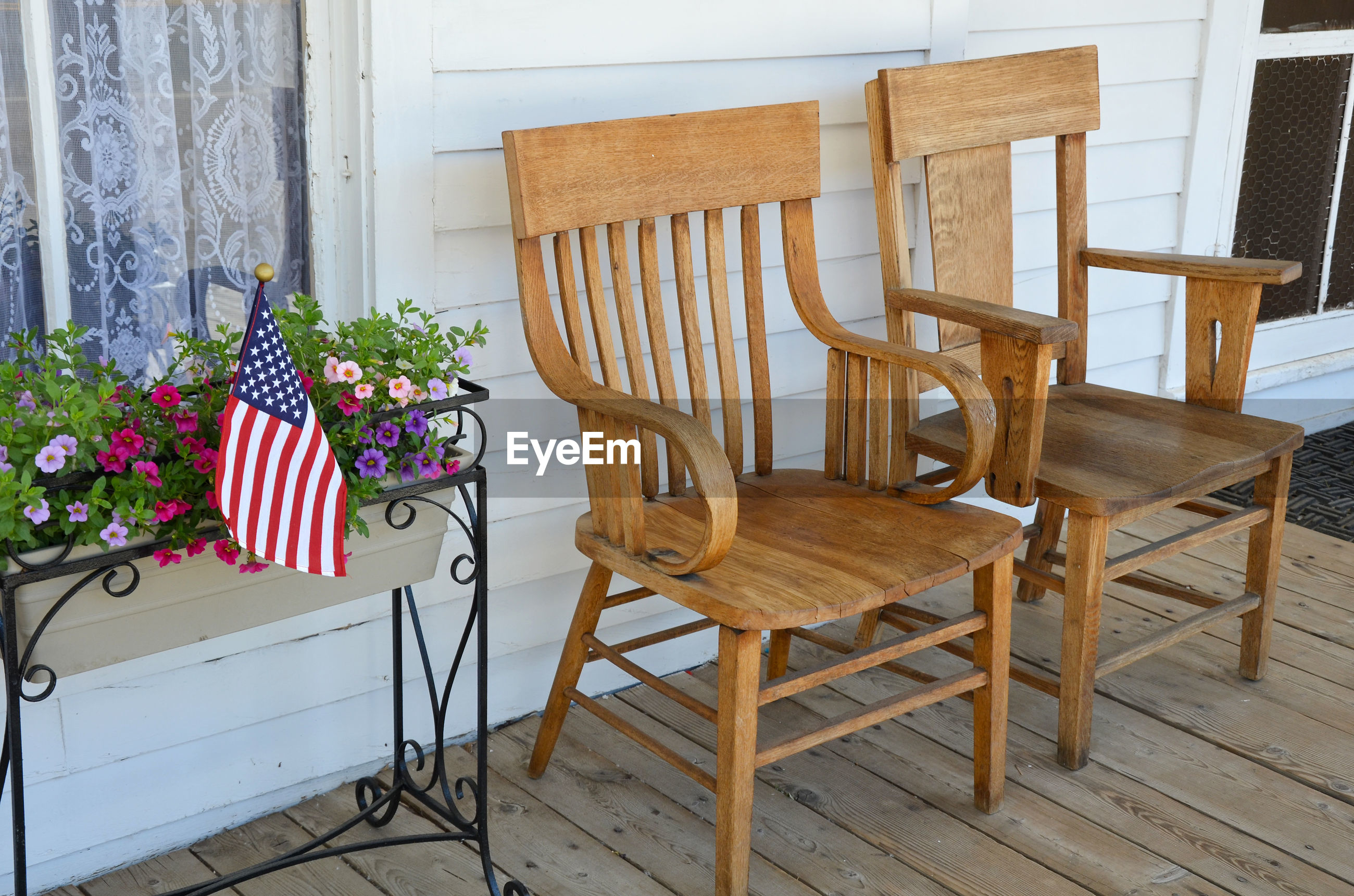 EMPTY CHAIRS AND TABLE BY POTTED PLANT ON FLOOR AT HOME