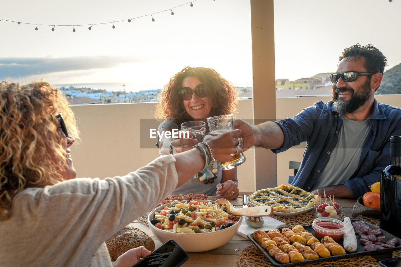 Friends Toasting Beer Glasses At Table In Terrace During Sunset