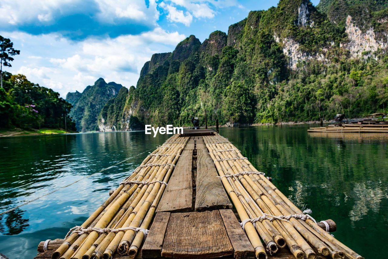 water, mountain, nautical vessel, sky, wood - material, nature, outdoors, cloud - sky, day, beauty in nature, scenics, wooden raft, bamboo - material, tree, lake, no people