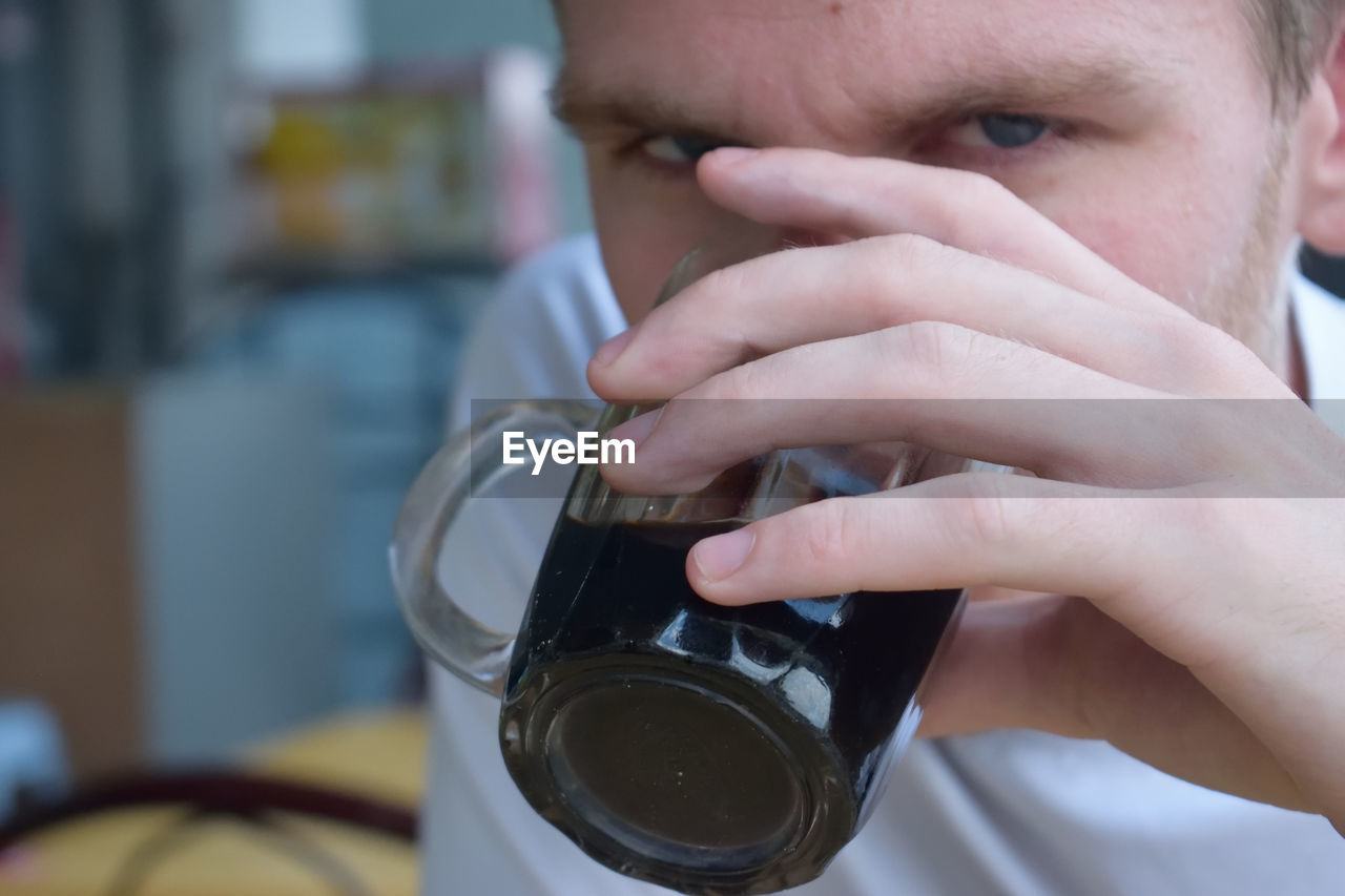 Close-up portrait of man drinking black coffee at cafe
