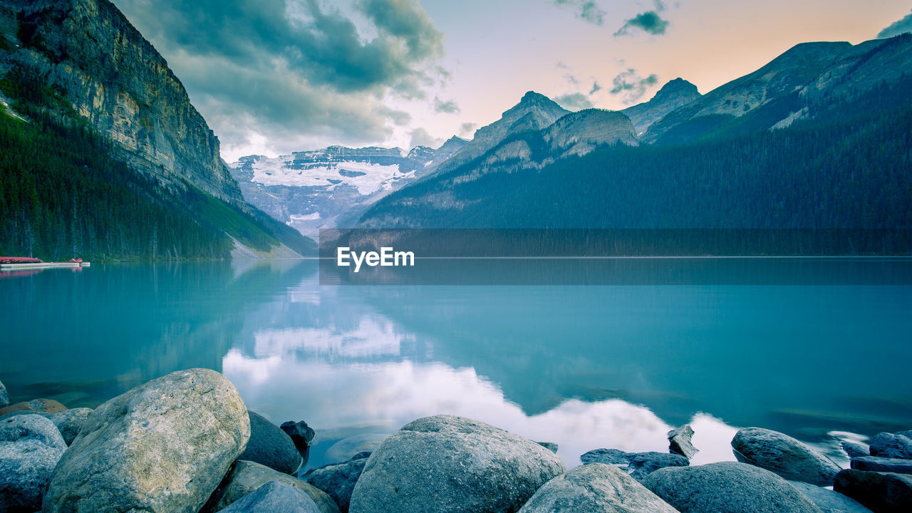 water, scenics - nature, beauty in nature, mountain, lake, sky, tranquil scene, tranquility, mountain range, rock, solid, rock - object, non-urban scene, reflection, idyllic, nature, cloud - sky, winter, no people, snowcapped mountain, outdoors, mountain peak