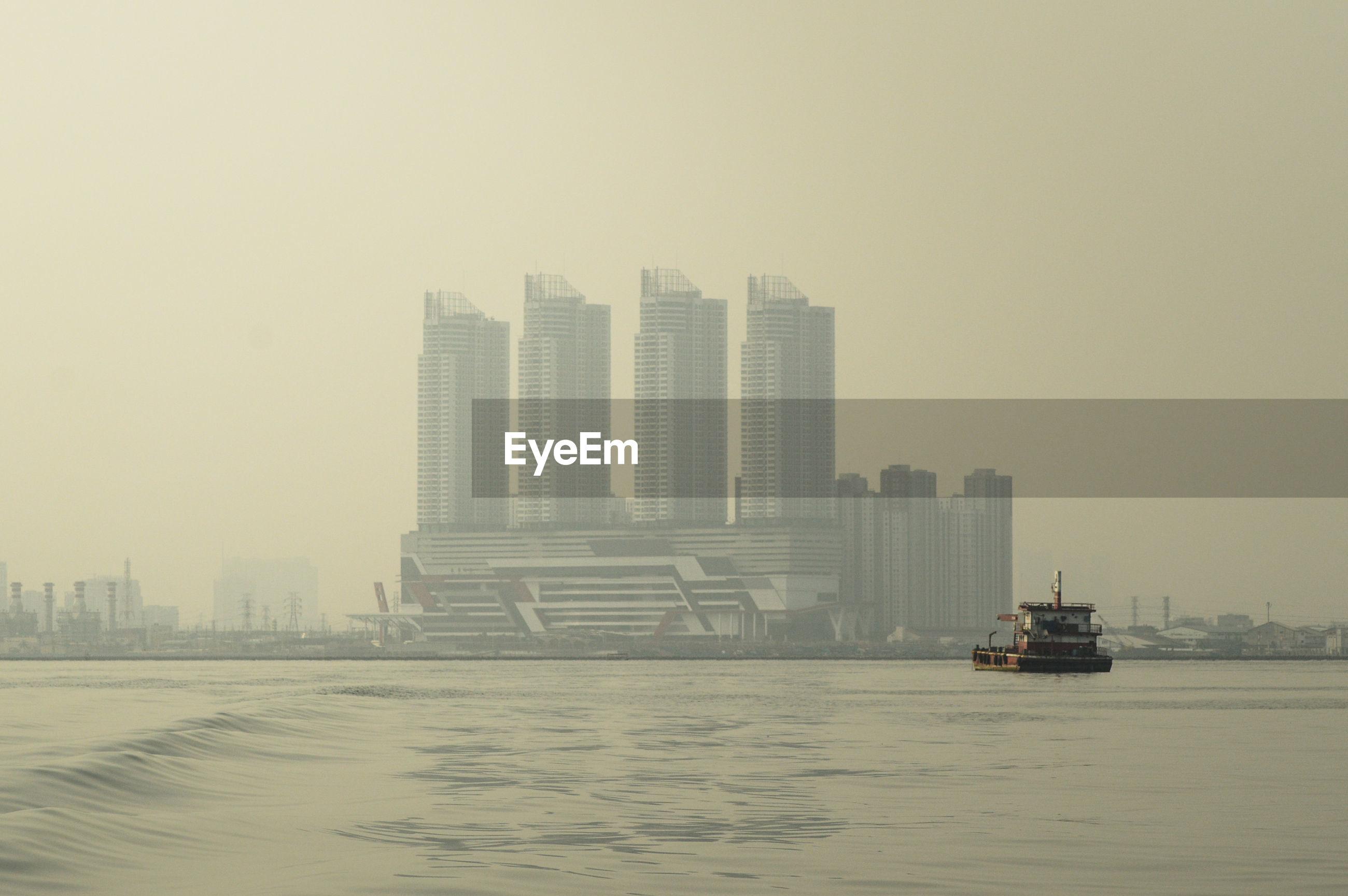 SHIP IN SEA AGAINST BUILDINGS IN CITY
