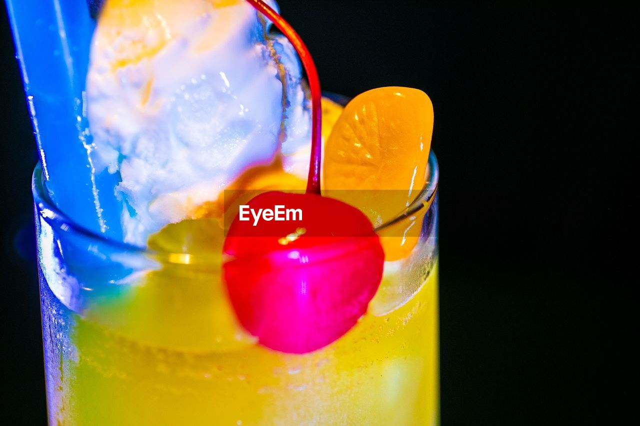 glass, food and drink, close-up, refreshment, no people, indoors, drinking glass, drink, freshness, yellow, food, still life, household equipment, cold temperature, indulgence, transparent, glass - material, cocktail, multi colored, ice cube, temptation, black background