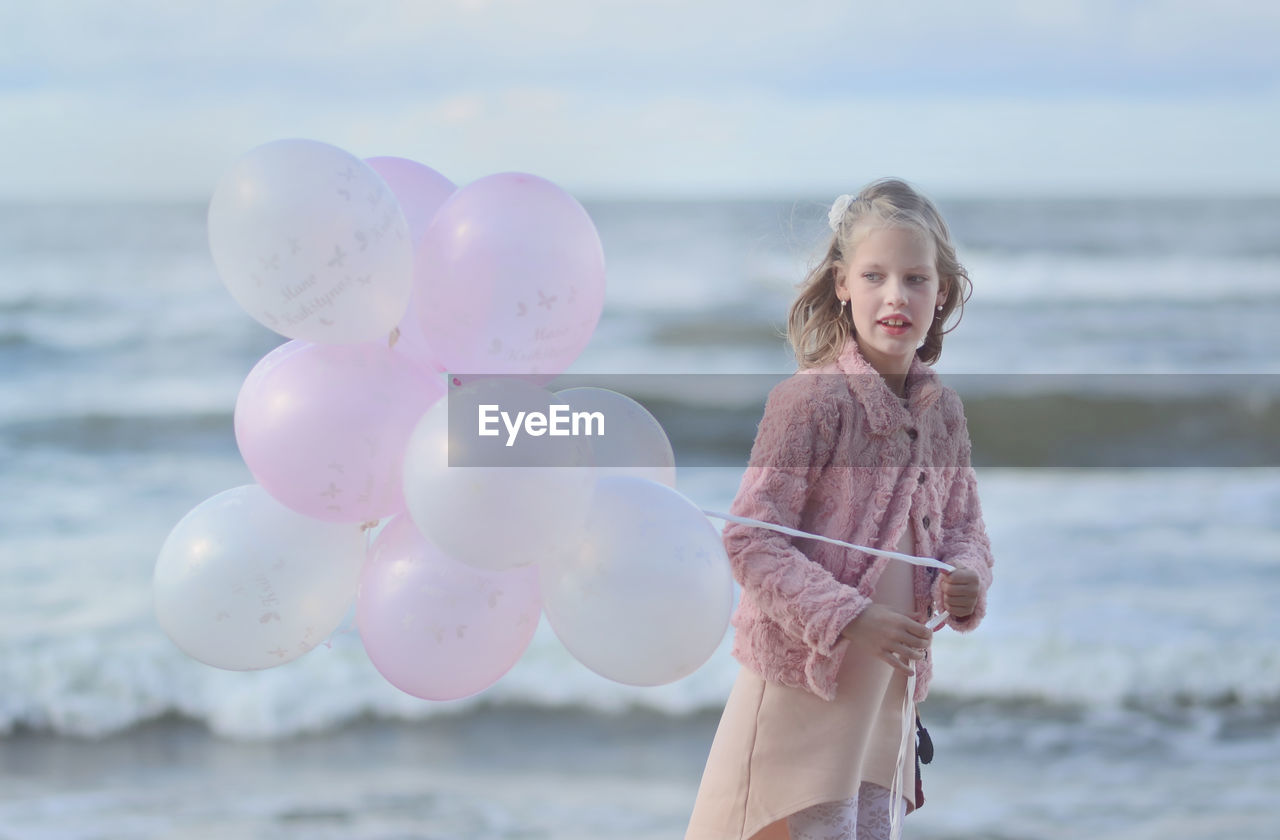 Girl Holding Balloon While Standing Against Sea At Beach