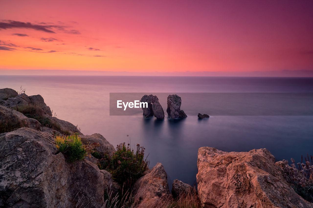 SCENIC VIEW OF ROCKS IN SEA AGAINST ROMANTIC SKY