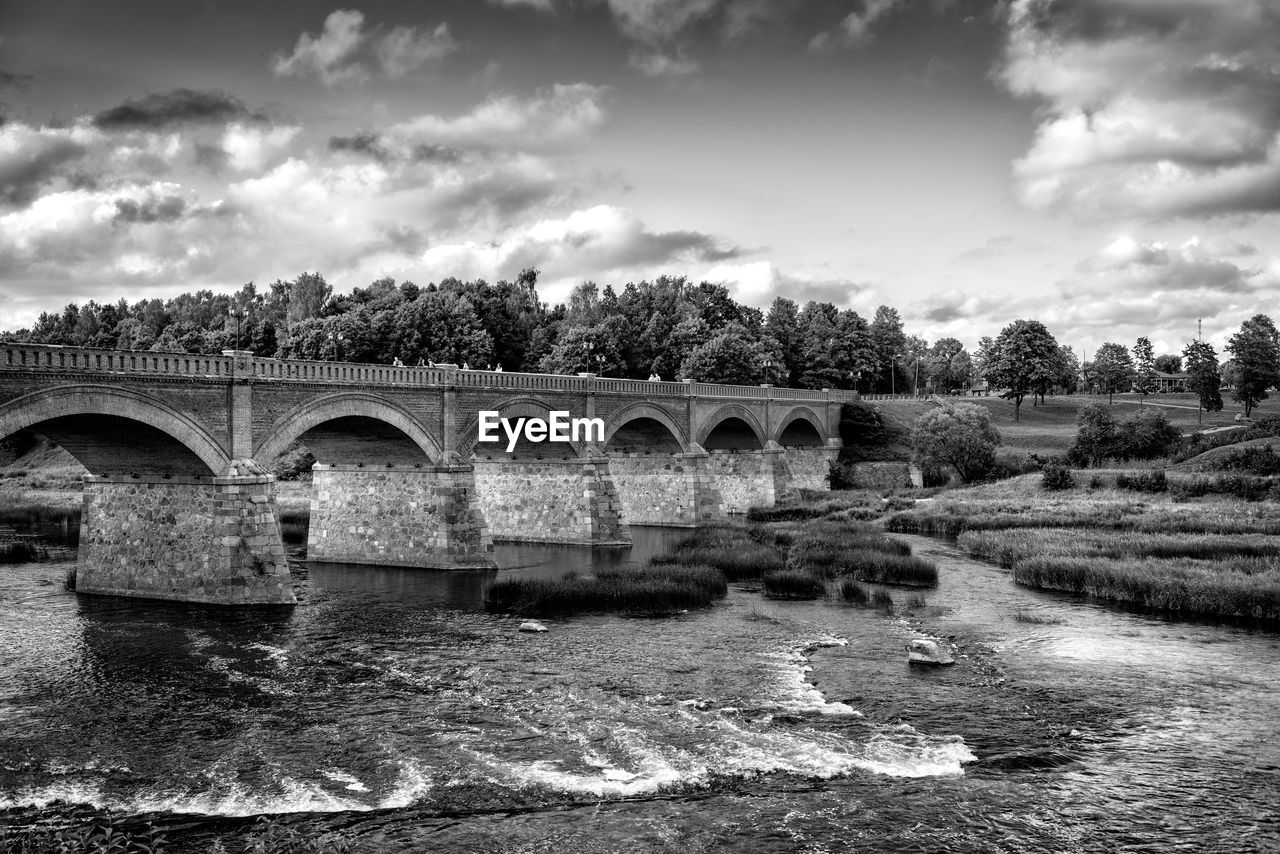 bridge - man made structure, water, connection, river, sky, architecture, cloud - sky, built structure, arch, day, motion, outdoors, tree, nature, no people, growth, waterfront, beauty in nature