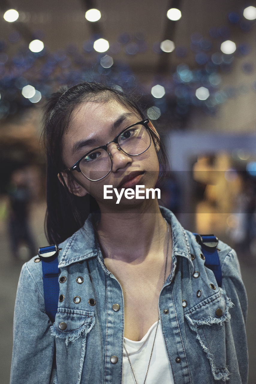 Close-Up Portrait Of Teenage Girl Wearing Eyeglasses Against Defocused Lights