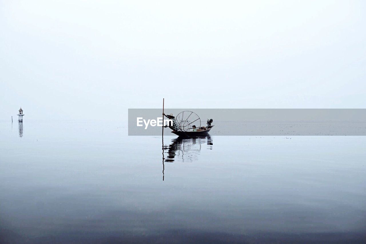 Fisherman In Boat With Conical Fishing Net