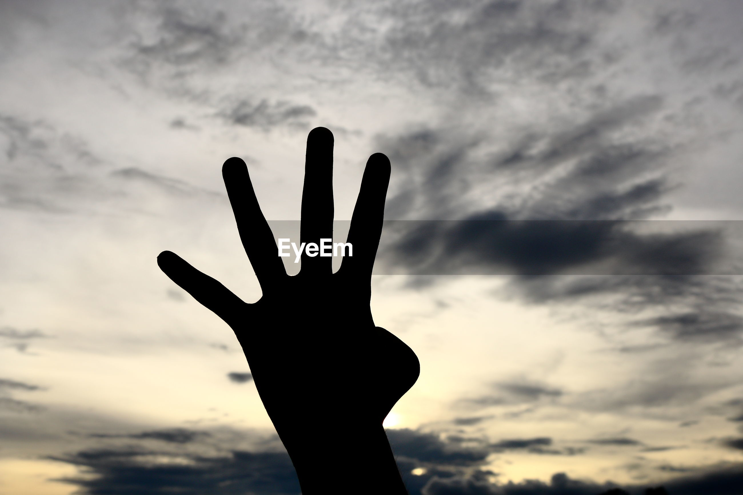 SILHOUETTE HAND AGAINST SKY