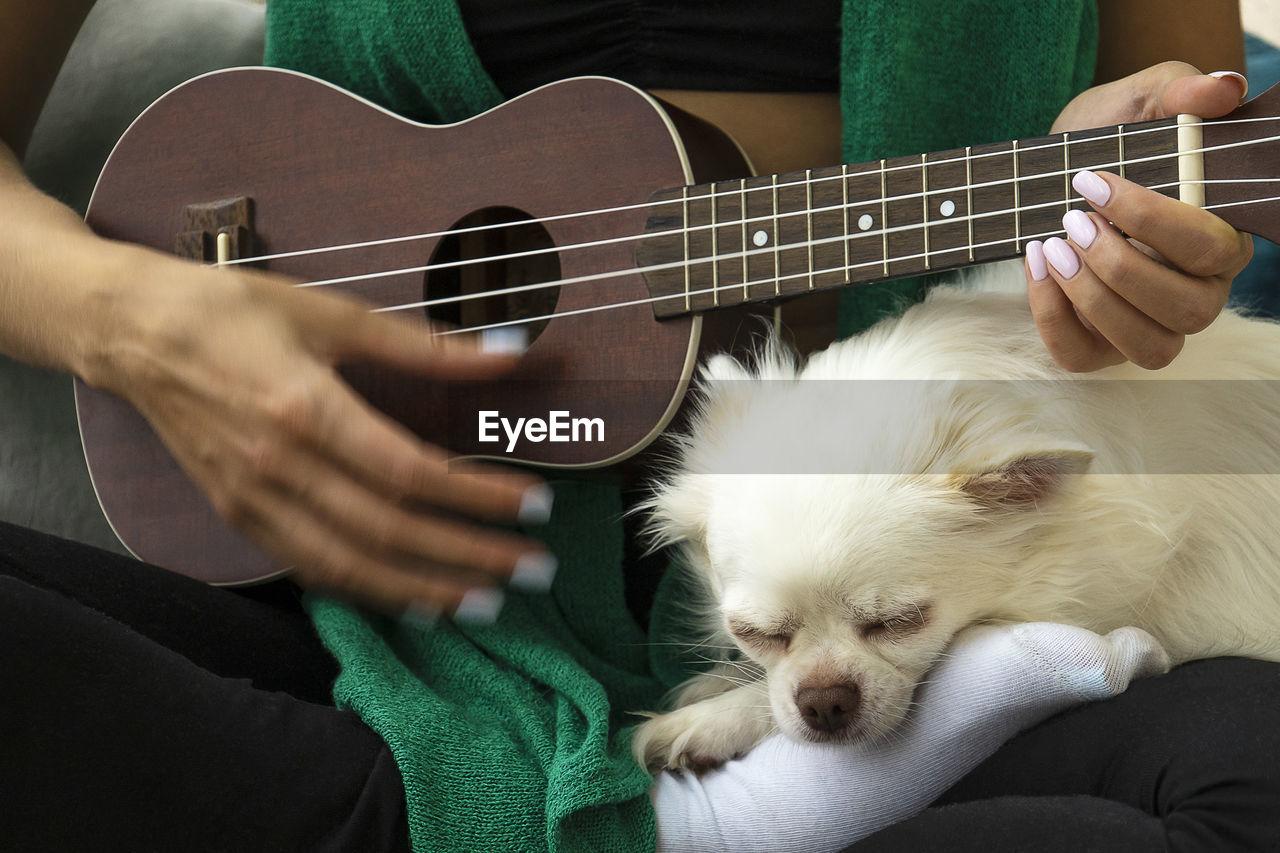 Woman playing ukulele. dog sleeping near. digital detox, simple pleasures, mental health concept.